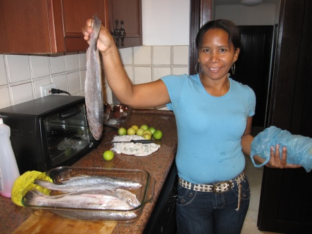 Gloria cooking fish in our kitchen.